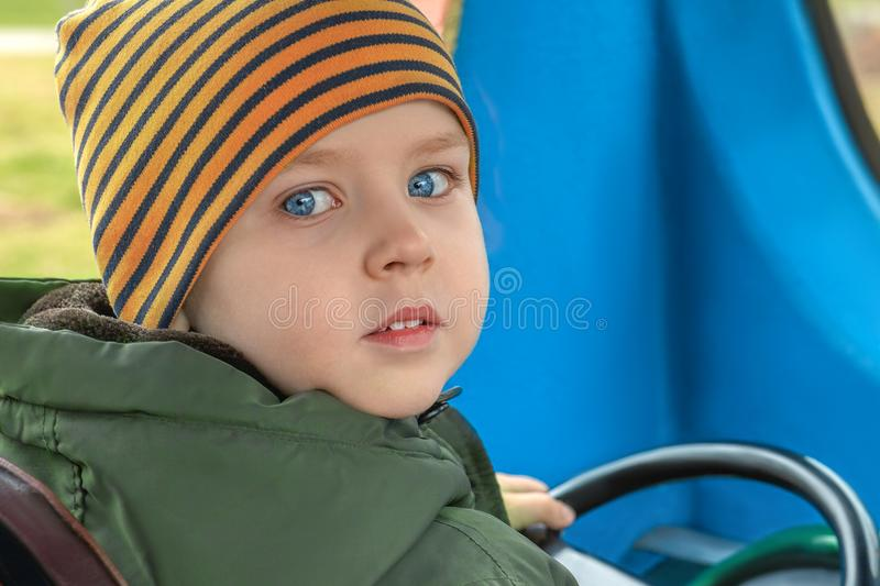 Little beautiful caucasian baby boy with bright blue eyes behind the wheel of the electric vehicle in a playground. Driving training, curiosity look. Spring royalty free stock images