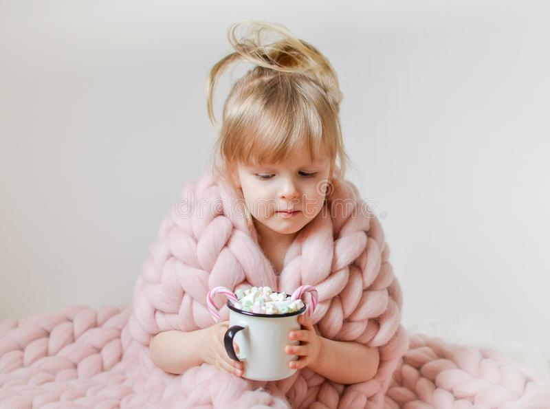 Little Beautiful Caucasian Girl Holding Cup with Hot Chocolate Waiting for Christmas and New Year, Merino Woolen Blanket Pastel Pi stock photo