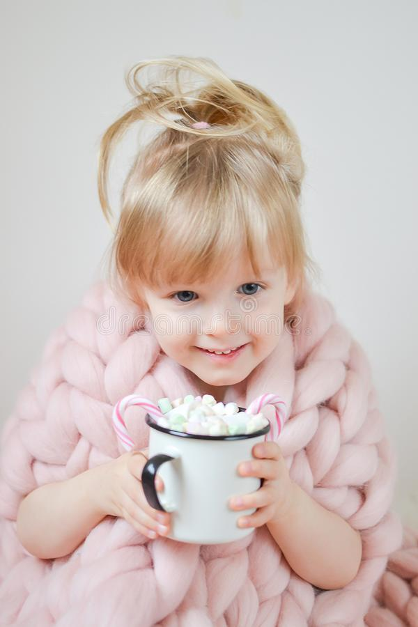 Little Beautiful Caucasian Girl Holding Cup with Hot Chocolate Waiting for Christmas and New Year, Merino Woolen Blanket Pastel Pi royalty free stock photo