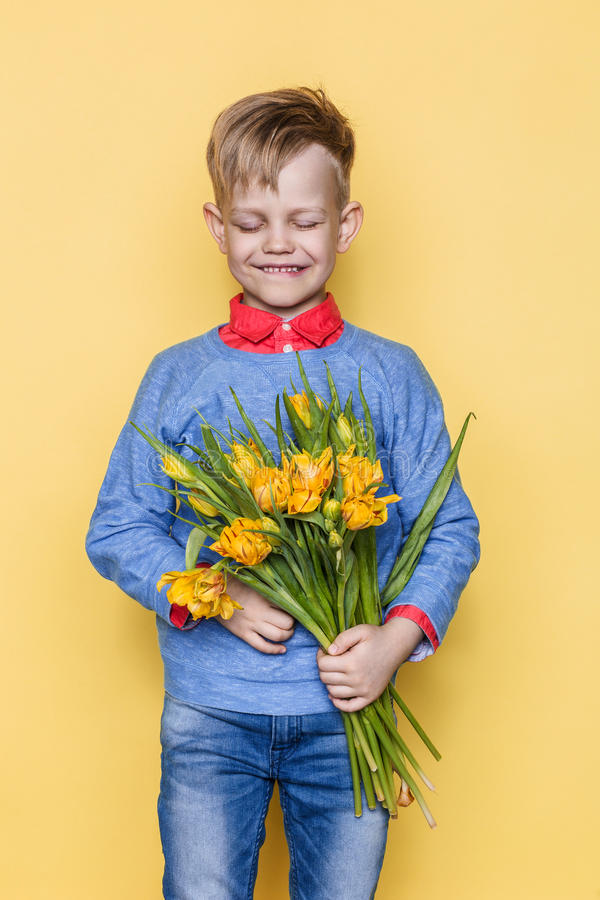 Little beautiful child with a bouquet of tulips. Son gives mom flowers on Women`s Day, Mother`s Day. Birthday. Valentine`s day. Sp stock photos