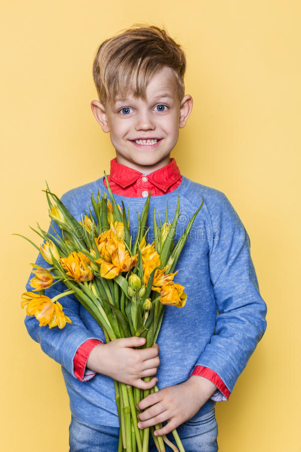 Little beautiful child with a bouquet of tulips. Son gives mom flowers on Women`s Day, Mother`s Day. Birthday. Valentine`s day. Sp stock images