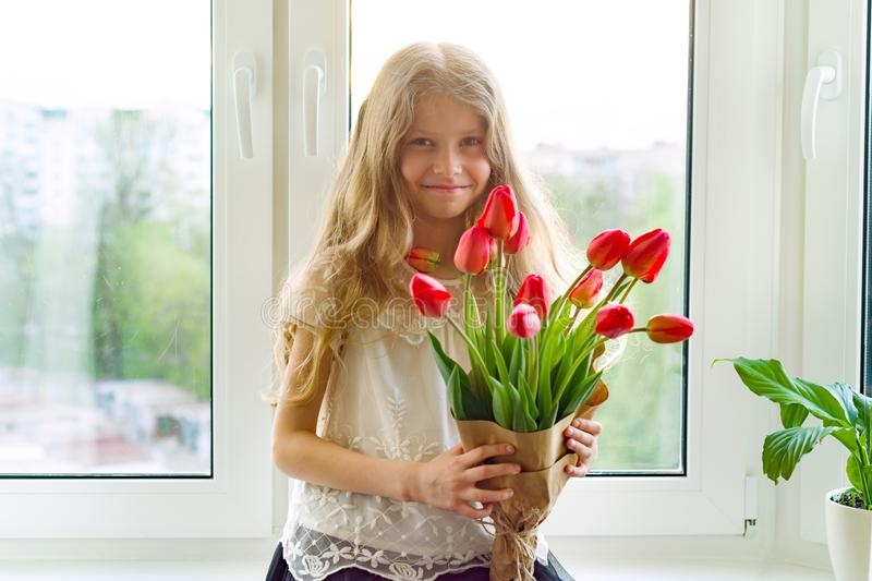 Little beautiful child girl with bouquet of red tulips flowers at home near the window, present for mother day. Gift, surprise, stock photos