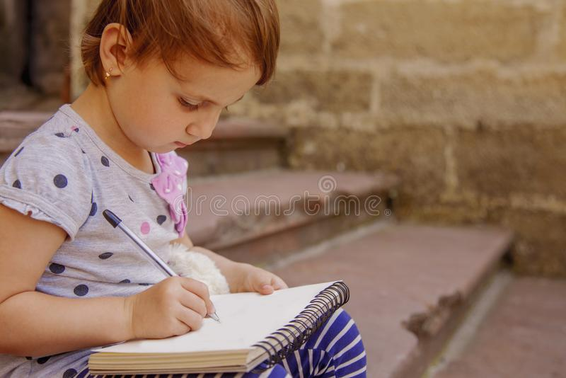 Little beautiful child girl writing a letter. stock photo