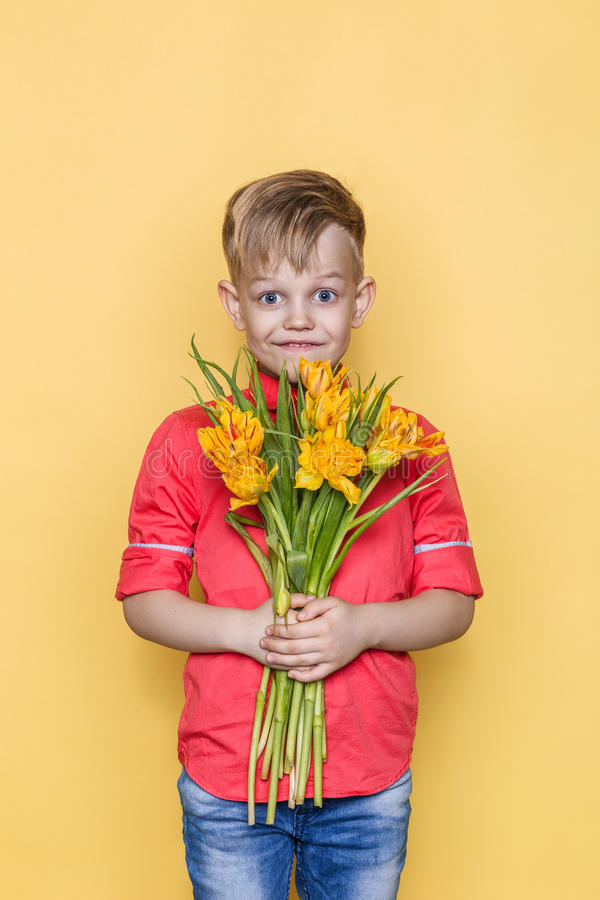 Little beautiful child with pink shirt gives a bouquet of flowers on Women`s Day, Mother`s Day. Birthday. Valentine`s day. Spring. royalty free stock image