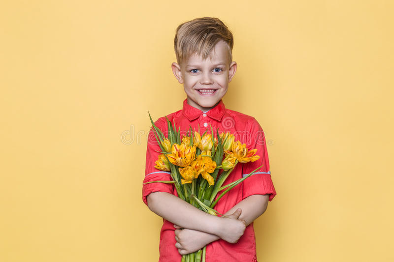 Little beautiful child with pink shirt gives a bouquet of flowers on Women`s Day, Mother`s Day. Birthday. Valentine`s day. Spring. stock images