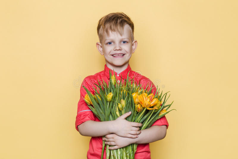Little beautiful child with pink shirt gives a bouquet of tulips on Women`s Day, Mother`s Day. Birthday. Valentine`s day. Spring. stock photos