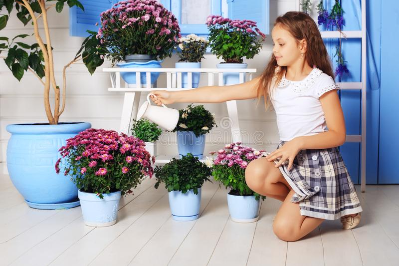 Little beautiful daughter watering flowerpots. The concept of work and lifestyle. stock images