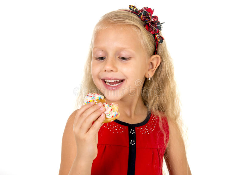 Little beautiful female child with long blonde hair and red dres. S eating sugar donut with toppings delighted and happy isolated on white background in children royalty free stock image