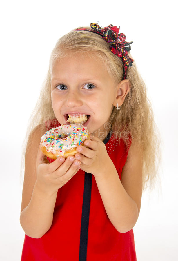 Little beautiful female child with long blonde hair and red dress eating sugar donut with toppings delighted and happy. Isolated on white background in children stock images