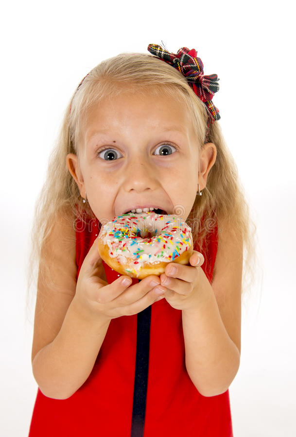 Little beautiful female child with long blonde hair and red dress eating sugar donut with toppings delighted and happy. Isolated on white background in children royalty free stock images