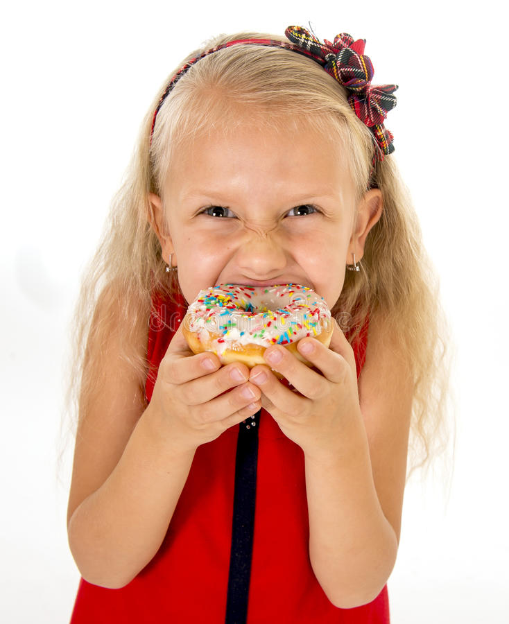Little beautiful female child with long blonde hair and red dress eating sugar donut. With toppings delighted and happy on white background in children sweet stock photos