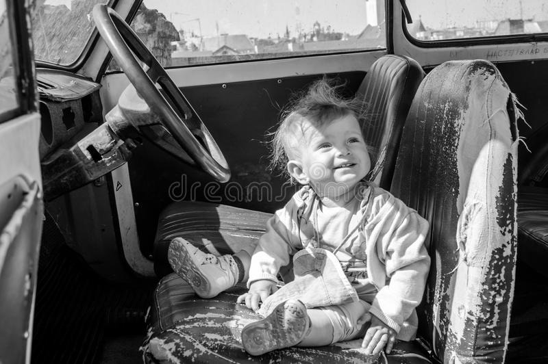 Little beautiful girl baby sitting on an old leaky leather seat behind the wheel of a vintage retro car black and white image. Little beautiful girl baby sitting stock image