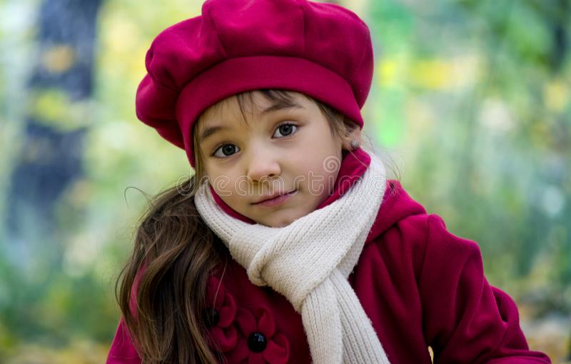 A little beautiful girl with big eyes, looks surprised, warm in autumn, in a pink beret and coat. royalty free stock photography