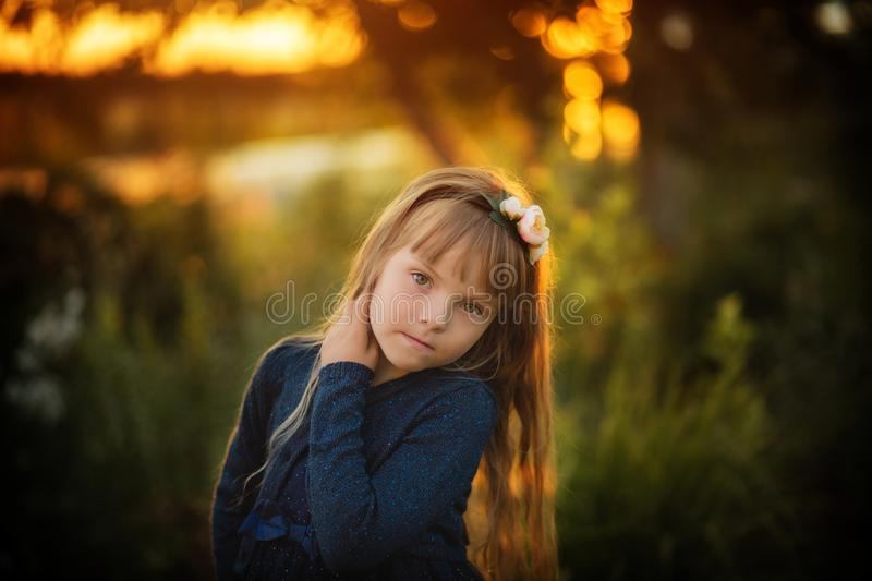 Little beautiful girl in blue dress outdoors at sunset royalty free stock image