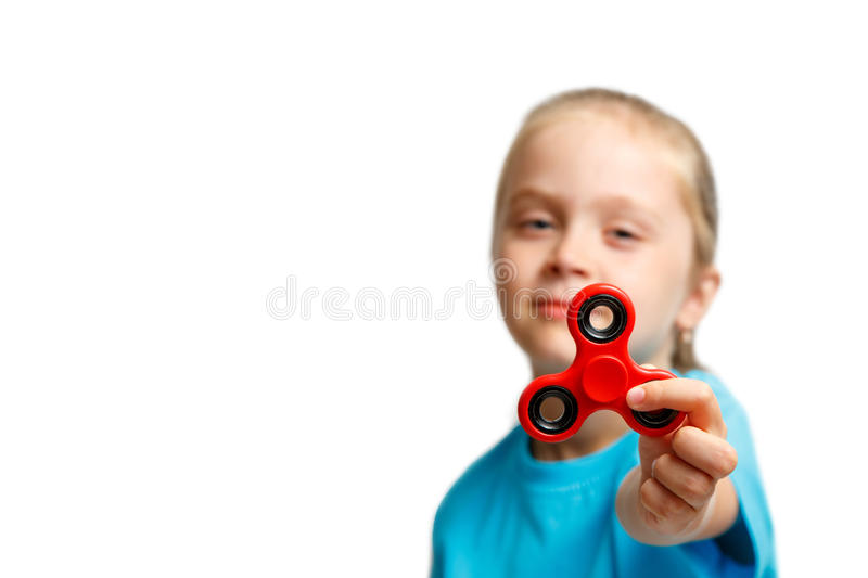 Little beautiful girl in blue t-shirt is playing red spinner in hand stock images