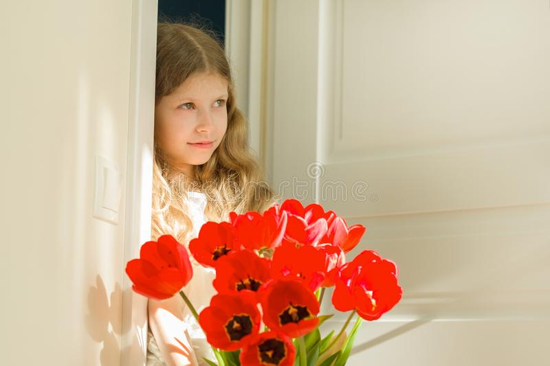 Little beautiful girl with bouquet of red tulips, present for mother, father day. Background sunny interior room royalty free stock photography