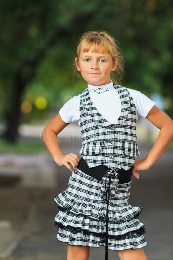 Little beautiful girl in a checkered school uniform royalty free stock images