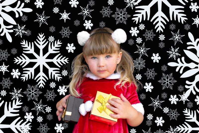 Little beautiful girl in a Christmas Santa suit, with fur balls on her head, holds gifts in her hands and rejoices royalty free stock photo
