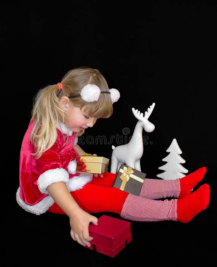 Little beautiful girl in a Christmas Santa suit, with fur balls on her head, holds gifts in her hands and rejoices stock image