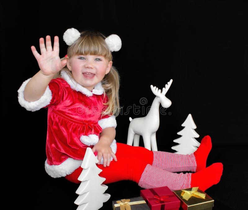 Little beautiful girl in a Christmas Santa suit, with fur balls on her head, holds gifts in her hands and rejoices. stock photos