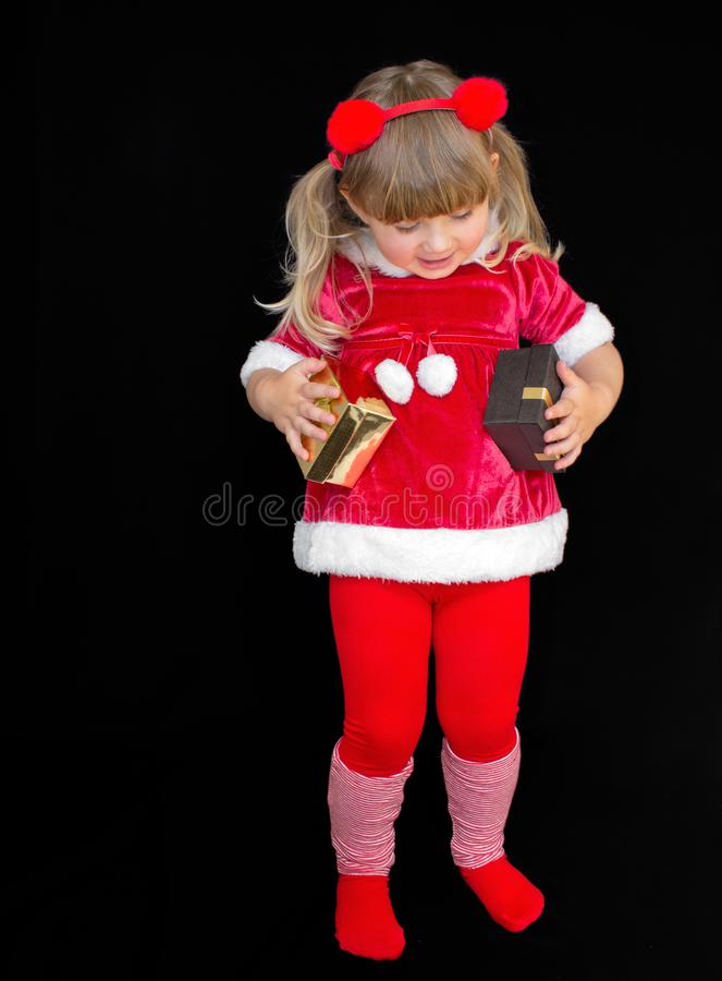 Little beautiful girl in a Christmas Santa suit, with fur balls on her head, holds gifts in her hands and rejoices. The concept of stock images