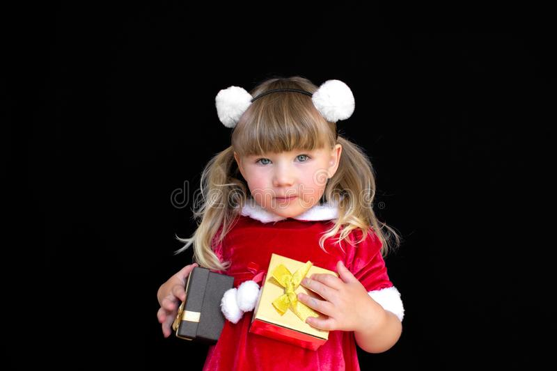 Little beautiful girl in a Christmas Santa suit, with fur balls on her head, holds gifts in her hands and rejoices. stock images