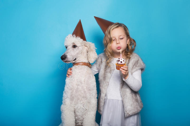 Little beautiful girl with dog celebrate birthday. Friendship. Love. Cake with candle. Studio portrait over blue background stock photos