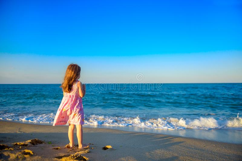 507ba10ad5545 Girl in dress walking on the beach. Little beautiful girl in dress walking  on the