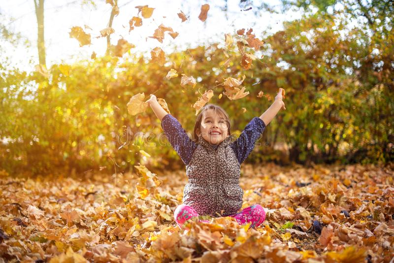 Little and beautiful girl enjoy autumn season and throw up leaves royalty free stock photo