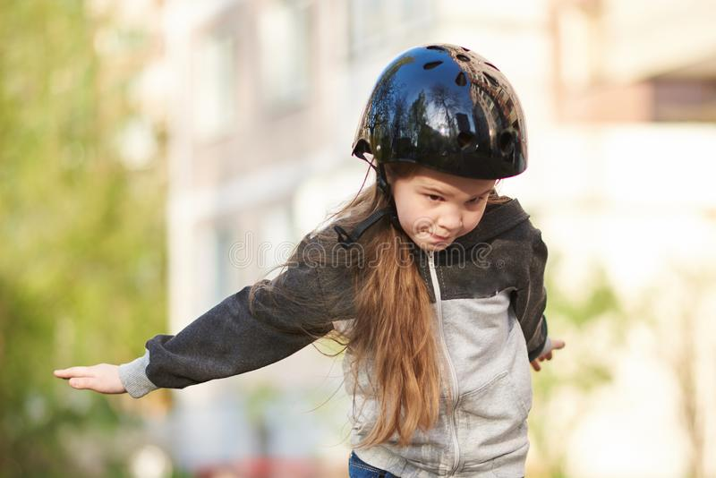 Little beautiful girl falls off a skateboard. For any purpose stock photos