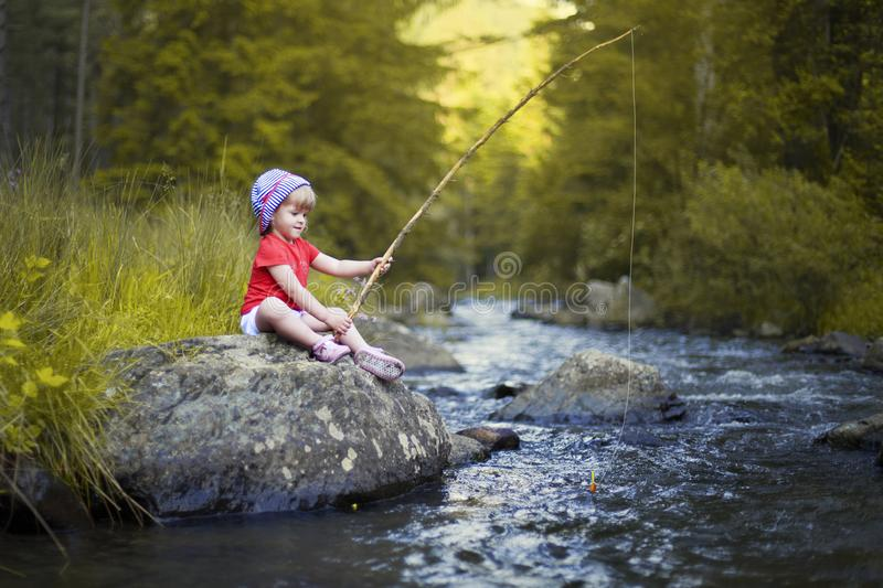 Little Girl Fishing on a Blue River. Little beautiful girl fishing on a blue river with a wooden stick and a string on a summer day with forest in background royalty free stock photos