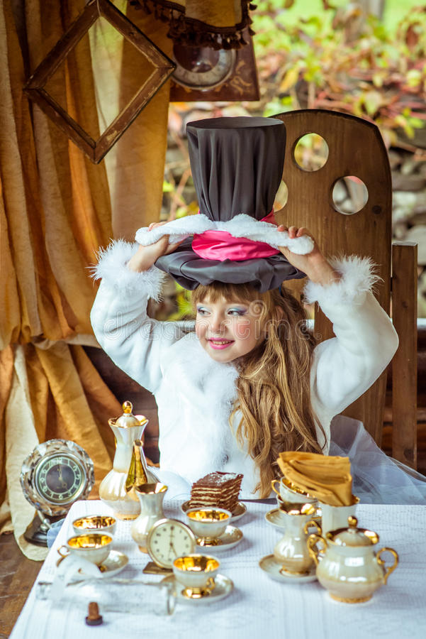 An little beautiful girl holding cylinder hat with ears like a rabbit over head at the table stock photography