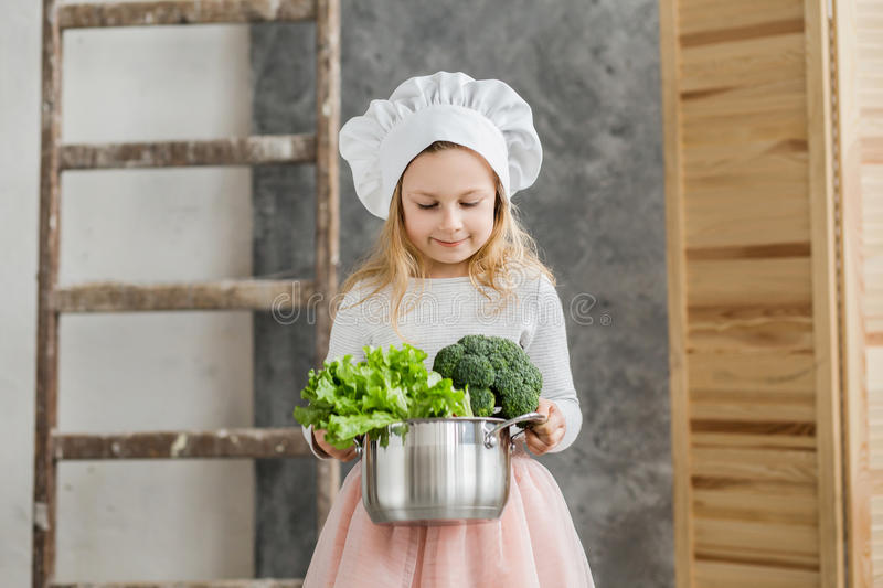 Little beautiful girl holding a pot full of vegetables. Healthy food. Harvest. Little housewife royalty free stock photos