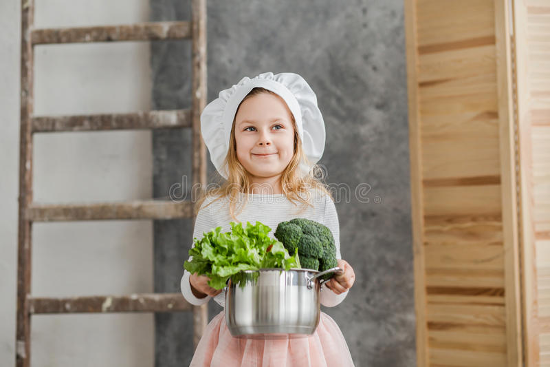 Little beautiful girl holding a pot full of vegetables. Healthy food. Harvest. Little housewife stock photo