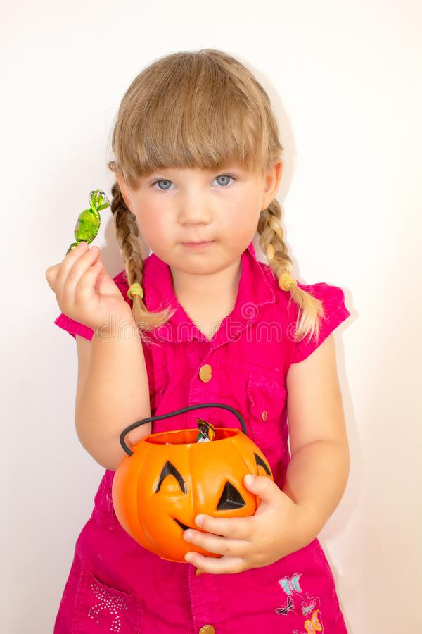 Little beautiful girl holding pumpkin with sweets in hands, on Halloween. stock photography