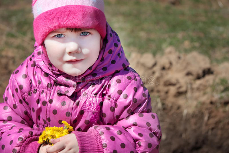 Little beautiful girl holds yellow flowers royalty free stock photography