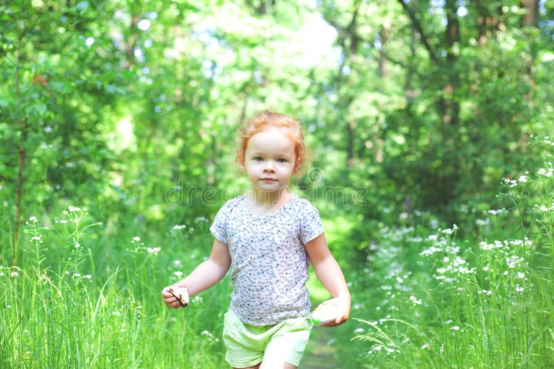 A little beautiful girl with light red hair is walking along a path in the forest. Girl of model appearance stock photography