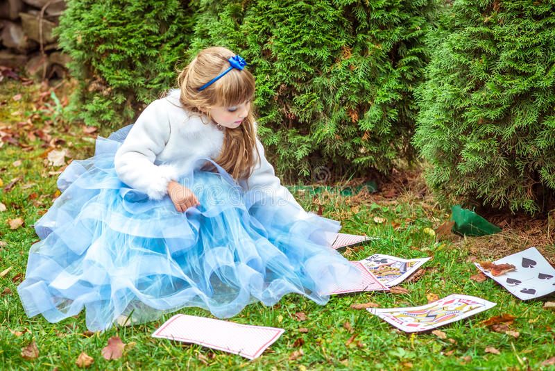 An little beautiful girl in a long blue dress sitting on the grass and playing with large game cards stock image