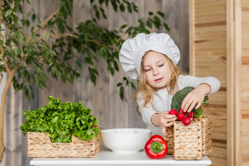 Little beautiful girl making vegetable salad in the kitchen. Healthy food. Little housewife stock photo