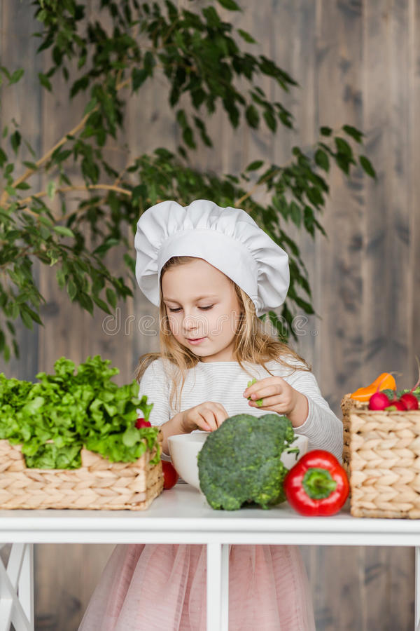 Little beautiful girl making vegetable salad in the kitchen. Healthy food. Little housewife royalty free stock photos