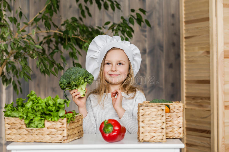 Little beautiful girl making vegetable salad in the kitchen. Healthy food. Little housewife stock images