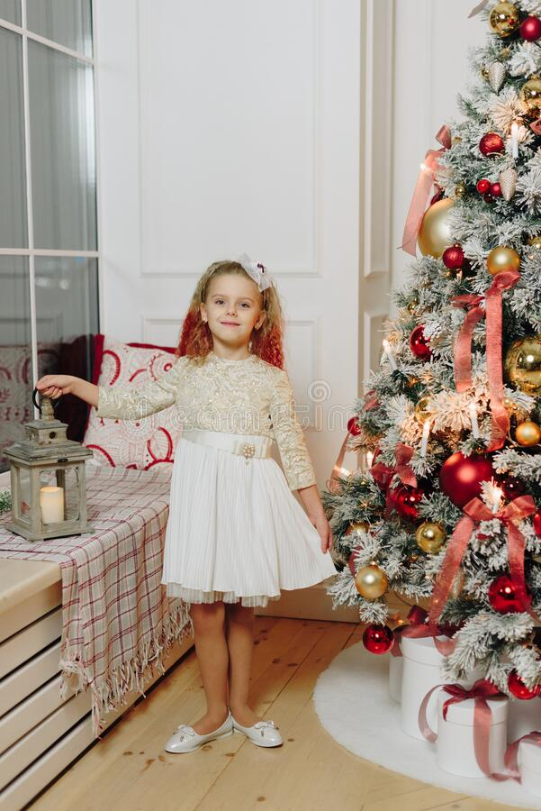 Free Little Beautiful Girl On The Background Of A Decorated Christmas Tree With Lights Royalty Free Stock Image - 169483616