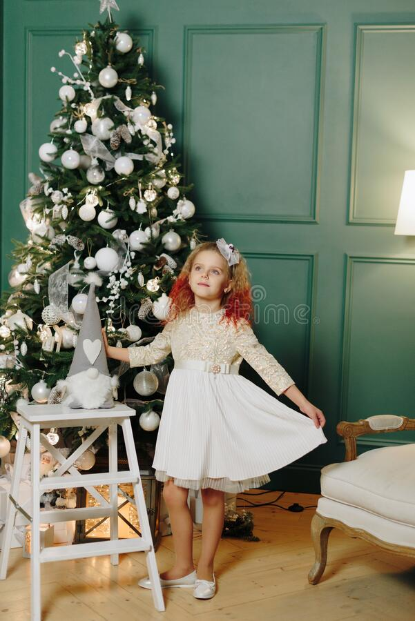 Free Little Beautiful Girl On The Background Of A Decorated Christmas Tree With Lights Royalty Free Stock Images - 169484409
