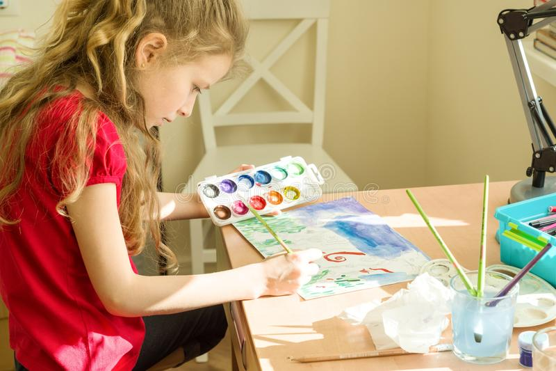 Little beautiful girl painting with watercolors, sitting at home at the table. Child creativity, recreation, development stock photos