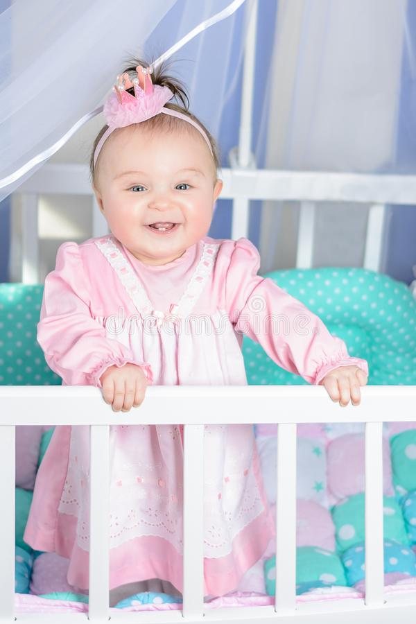 Little beautiful girl in a pink dress laughs in a baby bed stock image