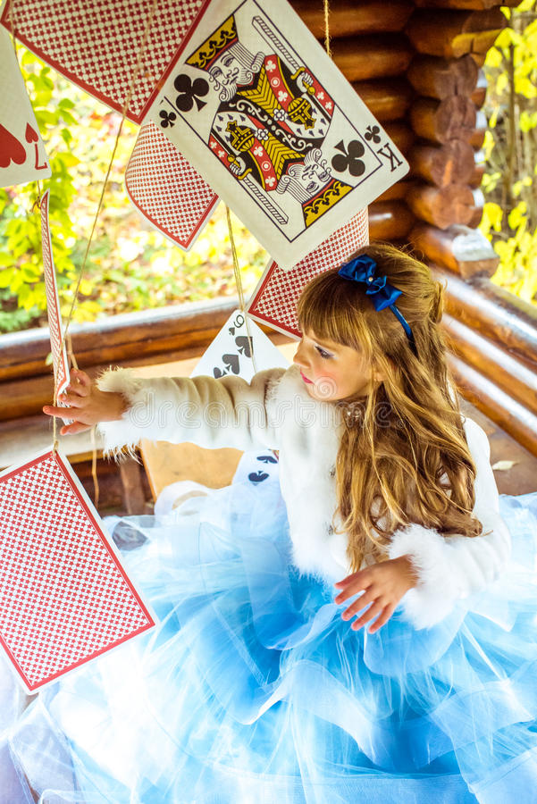 An little beautiful girl playing and dancing with large playing cards on the table stock photography