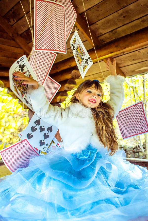 An little beautiful girl playing and dancing with large playing cards on the table royalty free stock photography