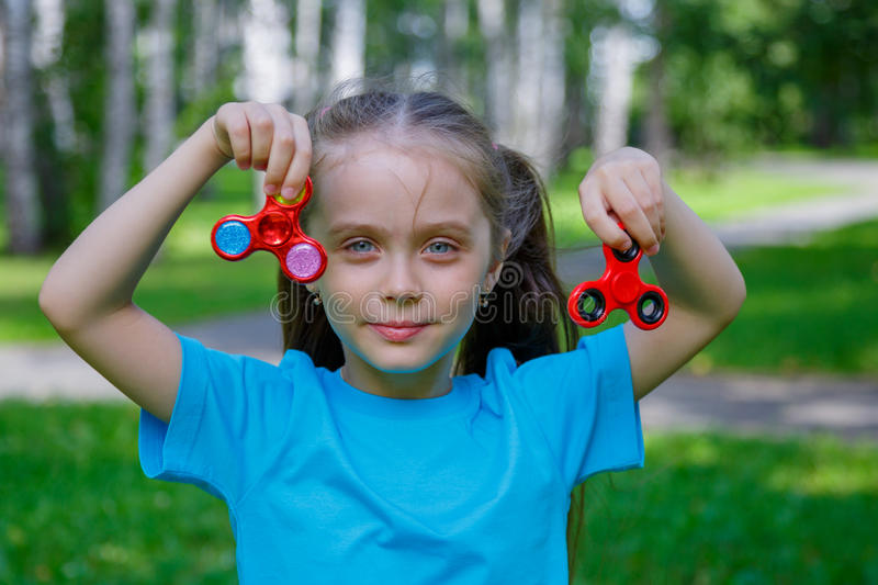 Little beautiful girl is playing with two spinners in hands royalty free stock photo
