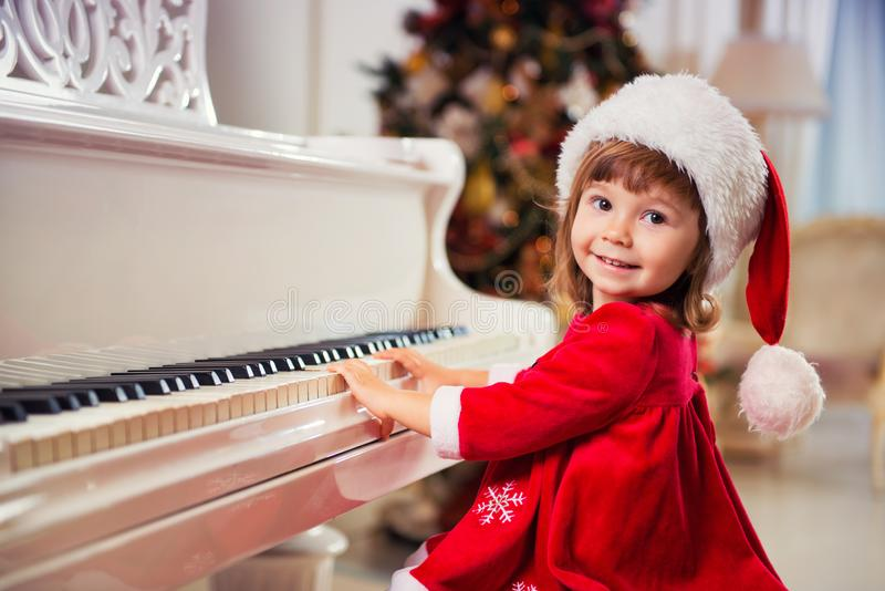 Little beautiful girl is playing on a white grand piano. royalty free stock photo