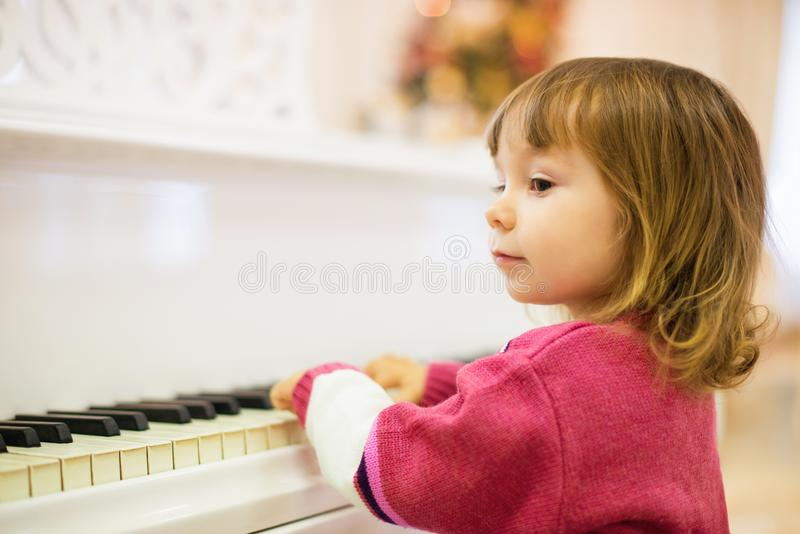 Little beautiful girl is playing on a white grand piano. stock photo